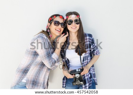 Two smiling young girls are standing in front of the white wall and listening to a music. One of them holing an old camera.