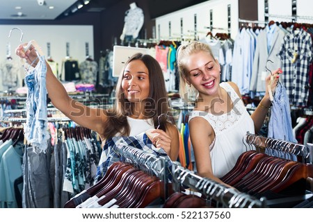 two smiling young girls shopping new pair of denim shorts together in clothes department