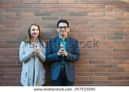 Two smiling young people holding ice cream cones standing near brick wall with copy space