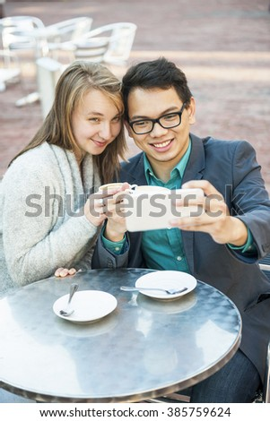 Two smiling young people looking into smartphone and taking a selfie while sitting at outdoor cafe table