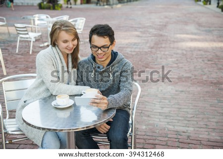 Two smiling young people looking into smartphone while sitting at a table in outdoor cafe with copy space