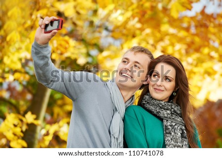 Two Smiling young people taking a picture with mobile phone in autumn park outdoors - stock photo