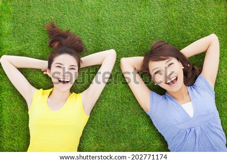 two smiling  young woman lying  on meadow - stock photo