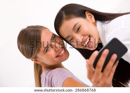 Two smiling young women taking self portrait with cell phone - stock photo