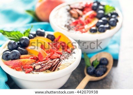 Two smoothie bowls with peaches, blueberries, Goji berries, chia and pecans with wooden spoon filled with blueberries, close up - stock photo