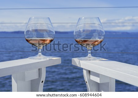 Two snifter glasses of brandy on a seaside deck