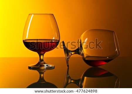 Two snifters of brandy on the reflective background