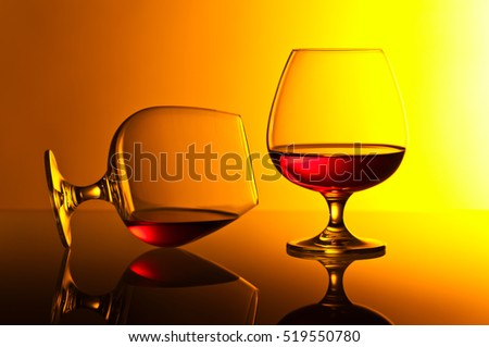 Two snifters of brandy on yellow background