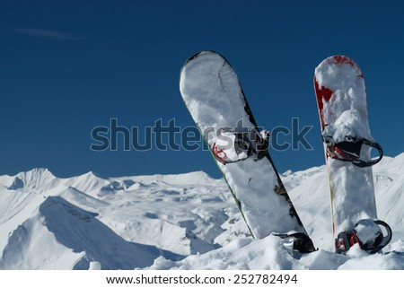 Two snow covered snowboards stood vertically in a wintry mountain range with blue sky background.