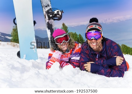 Two snowboarders lying together on the snow