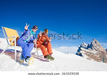 two snowboarders on top of the mountain having fun sitting on chair chaise lounge