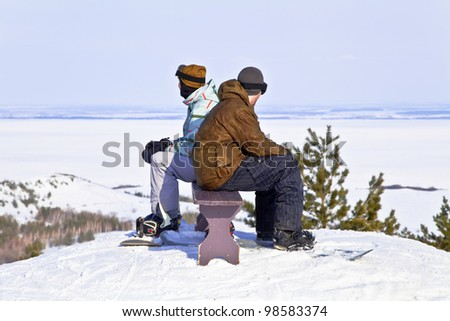Two snowboarders resting on top of mountain against the backdrop of a beautiful winter landscape. Back to back. - stock photo