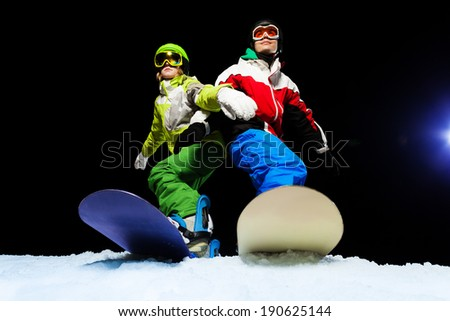 Two snowboarders wearing ski mask at night - stock photo
