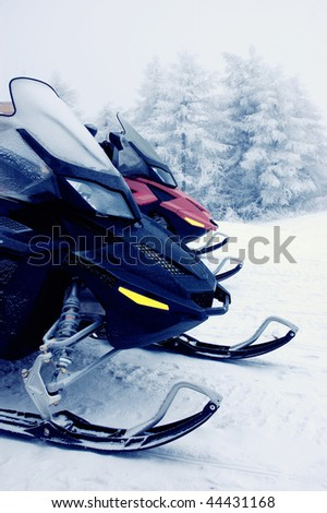 Two snowmobiles in the mountains - stock photo