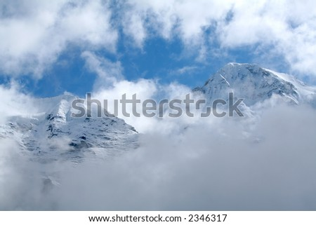 Two snowy mountain peaks showing through the clouds - stock photo