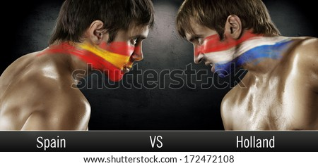 Two soccer fans with flags face to face. Spain and Holland, World Cup 2014 - stock photo