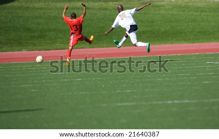 Two soccer players jumping wacky after the ball - stock photo