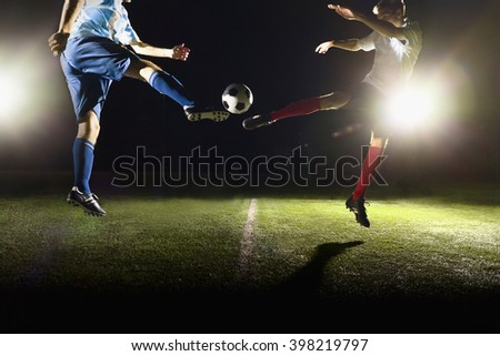 Two soccer players kicking a soccer ball
