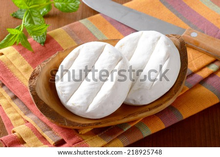 two soft cheeses with white mold on wooden bowl and striped tablecloth - stock photo
