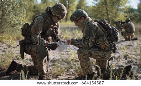 Two soldiers sitting in nature and using map and gps tracker for navigation.