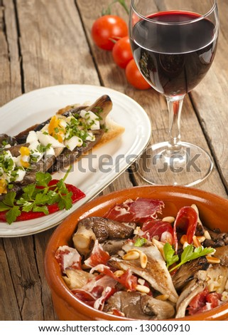Two Spanish tapas with oyster mushrooms (setas),  with serrano ham and with eggs on toast.  With a grass of red rioja wine. - stock photo