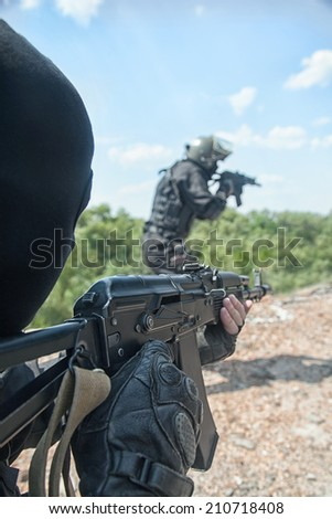 Two spec ops soldiers in black uniform in action - stock photo