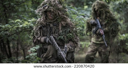 Two special forces soldiers on patrol in deep forest. Operators dressed in ghillie suits, holding assault rifles. - stock photo