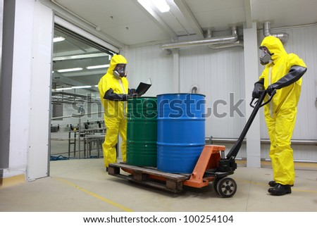 Two specialists in protective uniforms,masks,gloves and boots, dealing with barrels of toxic waste on forklift in factory - stock photo