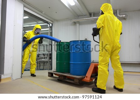Two specialists in protective uniforms,masks,gloves and boots  working with barrels of toxic waste  in factory - stock photo