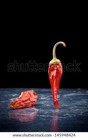 Two spicy chili peppers with reflection isolated on black background - stock photo