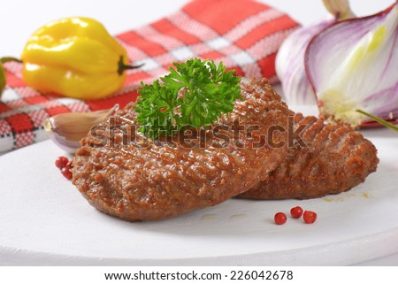 two spicy grilled burgers with onion and yellow pepper as a side dish - stock photo