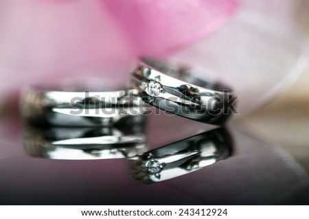 Two splendid wedding rings on a wedding day, shot on a reflective surface. Love concept. - stock photo