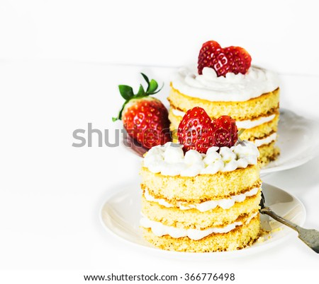 Two sponge cakes with cream and strawberries for Valentines day on  a white table. Selective focus.