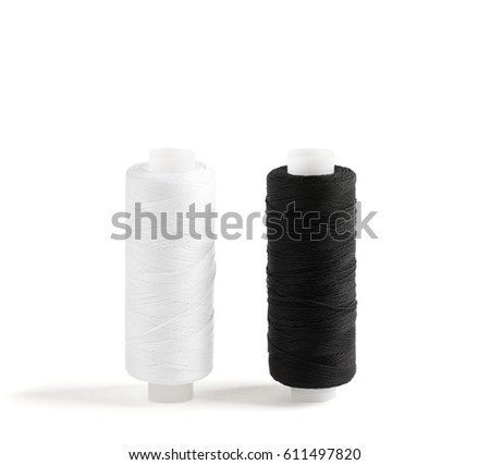 Two spools of cotton thread isolated on white. Black and white threads.