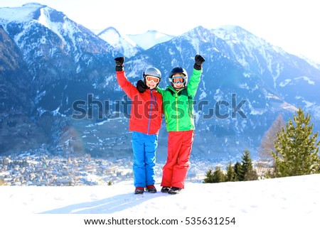 Two sportive boys enjoying active winter holidays. Sportive kids playing in the snow relaxing after day in ski or snowboard school. Beautiful Alps in the background.