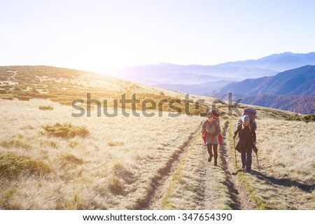 Two sports girls do Hiking in the mountains.