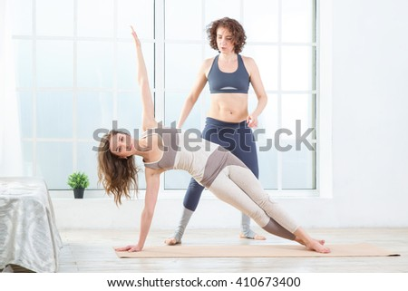Two sports woman. Fitness instructor. Lesson with a trainer. Two women doing stretching back to help complete the exercise. Restores health with your instructor in the  yoga studio. - stock photo