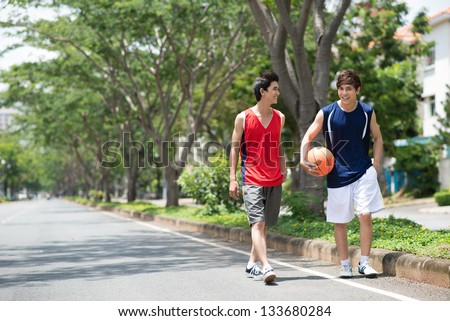Two sportsmen walking in the park with a ball - stock photo