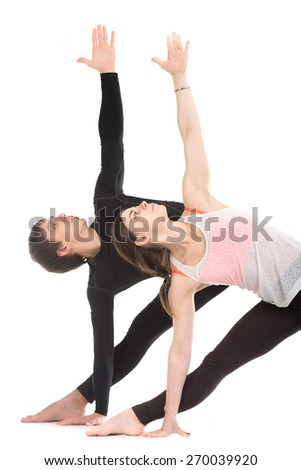 Two sporty people practice yoga with partner, couple doing stretching exercise, extended triangle pose, utthita trikonasana, close-up - stock photo