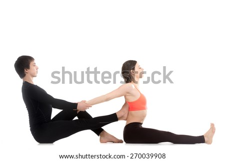 Two sporty people practicing yoga, young man helping his female partner to stretch for seated forward bend pose, paschimottanasana, side view - stock photo
