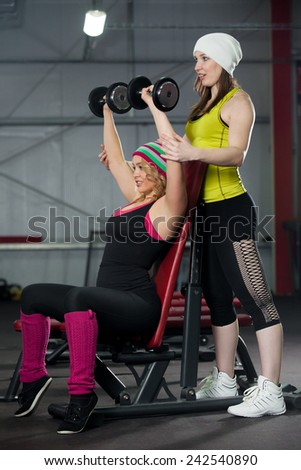 Two sporty pretty girls exercise together in gym, instructor assists to female bodybuilder in weightlifting