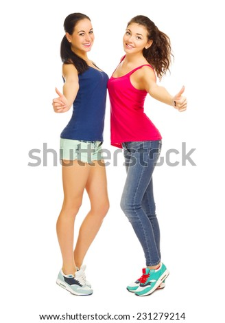 Two sporty young girls shows ok gesture isolated - stock photo