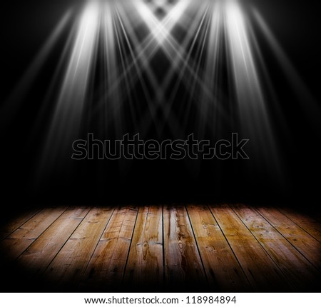 Two spot light on a wooden floor and a black background - stock photo
