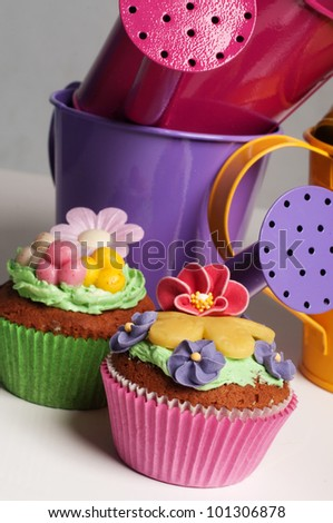 Two Spring cupcakes with flowers and egg decoration and watering cans - stock photo