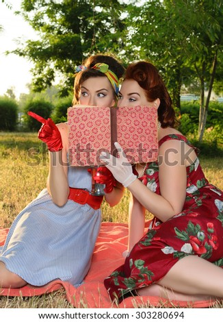 two spy girl hiding face behind the book retro - stock photo