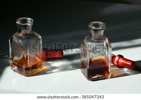 Two square apothecary eye dropper bottles with brown essential oils on white shelf in sunlight.