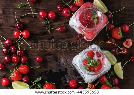 Two Square glass jars with homemade yogurt with mint, strawberry puree, cherry and chia seeds served with fresh berries  and sliced lime over dark wooden background. Top view. Space for text
