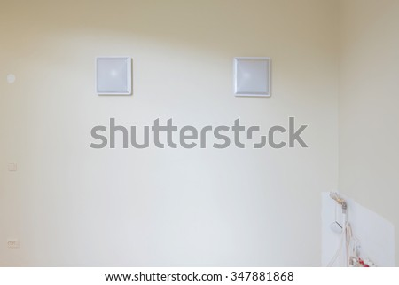 Two square lamps on the wall. The heating system are partially unfinished. - stock photo