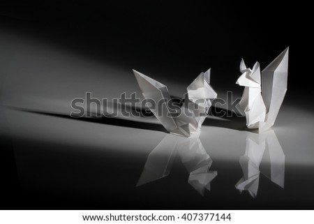 Two squirrels origami made of  white paper isolated on black background.
