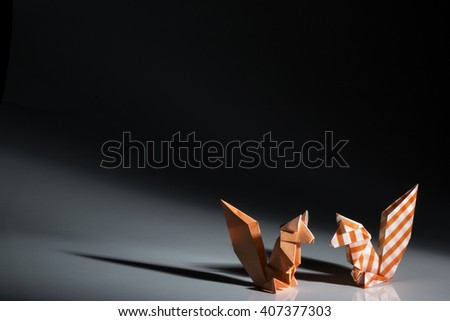 Two squirrels origami made orange papers isolated on black background.